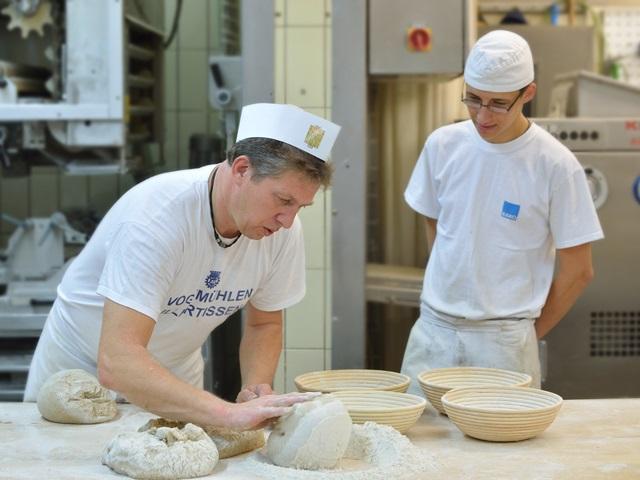 Ein Bäckermeister zeigt seinem Lehrling wie Brotteig geknetet wird.