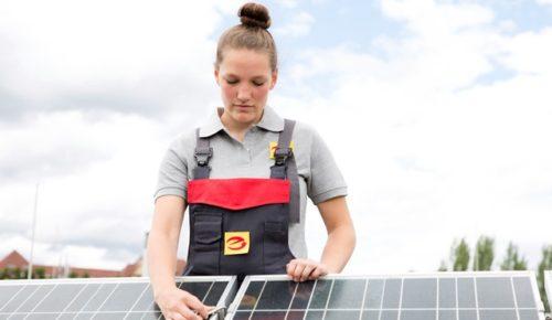 Eine Elektronikerin für Energie- und Gebäudetechnik wartet eine Solaranalage.
