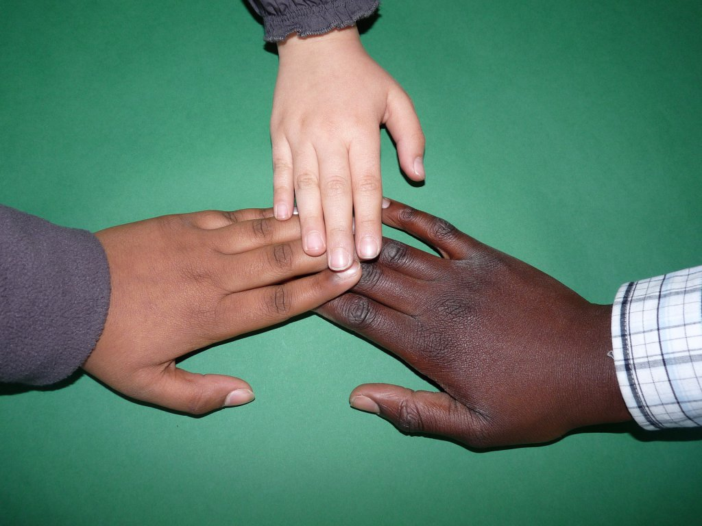 Illustration: Drei Hände verschiedener Hautfarbe zusammen. Bildquelle: Falco via pixabay